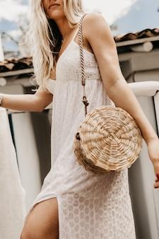 Вертикальный снимок блондинки в белом платье с соломенной сумкой на плече