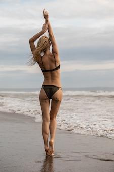 Вертикальный снимок блондинки, стоящей на пляже в черном купальнике под облачным небом