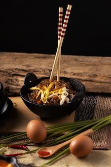木製のテーブルの上においしい食べ物と箸のボウルの垂直ショット