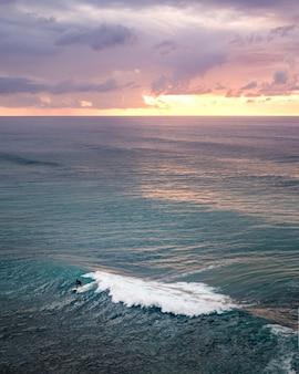 바다 위로 숨막히는 일몰 풍경의 세로 샷