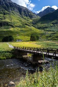 스코틀랜드의 산으로 둘러싸인 강 위에 다리의 세로 샷