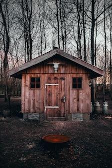 木々を背景にした木造の納屋の入り口にある水牛の頭蓋骨の垂直ショット