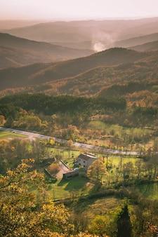 Вертикальный снимок здания и деревьев в гористой местности