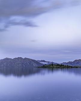 Вертикальный снимок спокойного озера с отражениями на горном хребте