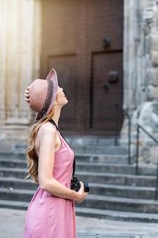 街の写真を撮る帽子をかぶっている白人の金髪のかわいい観光客の垂直ショット