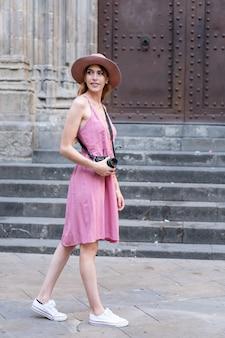 Вертикальный снимок красивой кавказской блондинки-туристки в шляпе, фотографирующей город