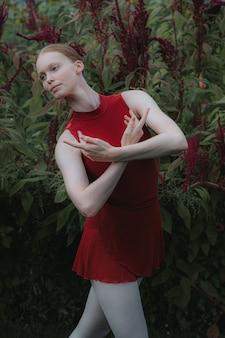 부르고뉴 의상을 입고 포즈를 취하는 백인 여성 발레 댄서의 세로 샷