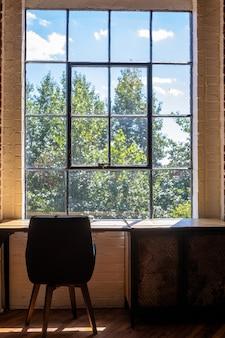Вертикальный снимок стула и стола возле большого окна с потрясающим видом на зелень снаружи