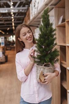 Вертикальный снимок веселой женщины, покупающей новогоднюю елку в супермаркете товаров для дома