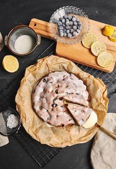Вертикальный снимок вишневого торта со сливками и ингредиентами сбоку на черном