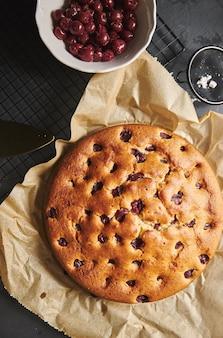 Вертикальный снимок вишневого торта с сахарной пудрой и ингредиентами сбоку
