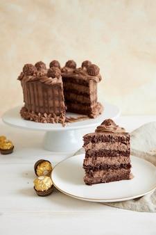 초콜릿 케이크의 세로 샷과 초콜릿 몇 조각 옆에 접시에 슬라이스