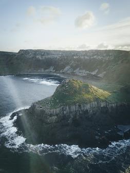 雲と澄んだ空の下で水辺の崖の垂直ショット