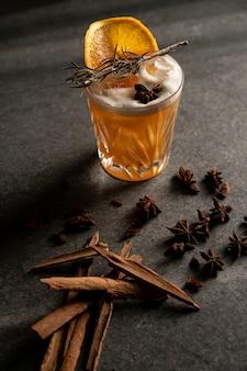 Вертикальный снимок коктейля с ломтиком апельсина и сухими травами рядом с палочками корицы