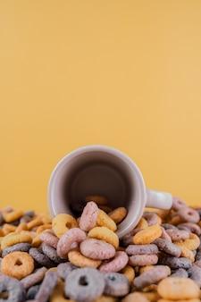 커피 컵에서 흘리 고 다채로운 시리얼의 세로 샷
