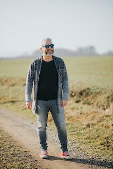 Вертикальный снимок уверенного в себе человека с седыми волосами, смеющегося и смотрящего в сторону на фоне поля