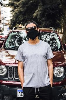 야외에서 얼굴 마스크를 쓰고 멋진 젊은 남자의 세로 샷-새로운 정상의 개념