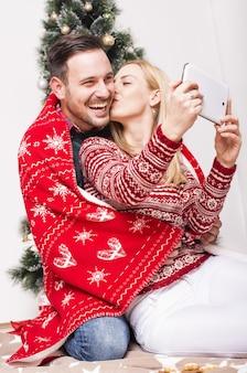 クリスマス休暇中にお互いの伴奏を楽しんでいるカップルの垂直ショット