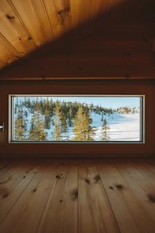 노르웨이의 눈으로 덮여 숲의 전망이있는 창문이있는 아늑한 다락방의 세로 샷