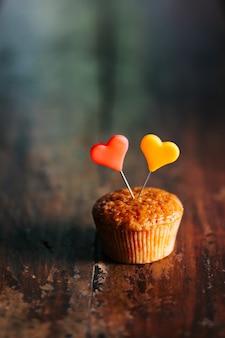 Вертикальный снимок кекса с красочными сердечками на нем