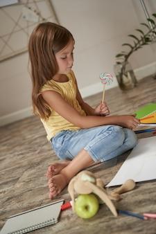 사탕을 들고 다채로운 연필로 그리는 귀여운 백인 소녀의 세로 샷