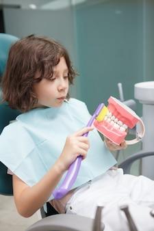 歯科医院で歯ブラシで顎モデルをブラッシングするかわいい少年の垂直ショット