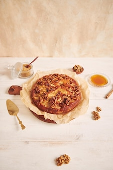白いテーブルの上の材料に囲まれた蜂蜜とおいしいリンゴクルミケーキの垂直ショット