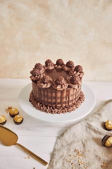 いくつかのチョコレートの横にあるプレート上のおいしいチョコレートケーキの垂直ショット
