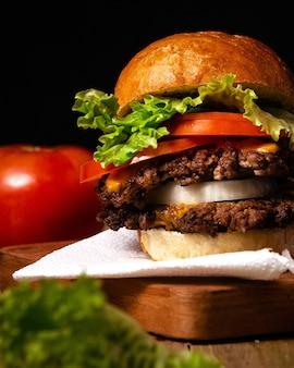 검은색 벽이 있는 나무 접시에 있는 맛있는 햄버거의 수직 샷