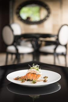 Вертикальный снимок блюда с креветками на белой тарелке