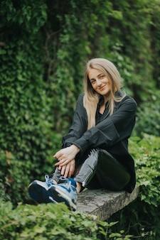 Вертикальный снимок модной кавказской блондинки, позирующей в окружении зелени