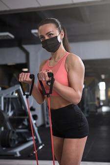 체육관에서 저항 밴드와 함께 운동하는 얼굴 마스크를 착용하는 여성 운동 선수의 세로 샷
