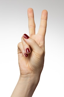 平和の手のサインと女性の手の垂直ショット