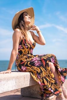 スペインで撮影された花のサンドレスと海のそばに座っている帽子の女性の垂直ショット