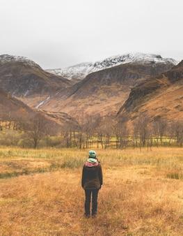 山の下のフィールドの中央に立っている帽子とジャケットの女性の垂直ショット