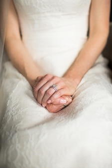 Вертикальный снимок женщины в длинном белом платье, сидящей, положив руки на колени