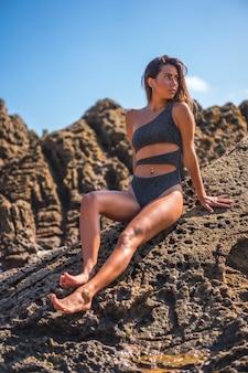 Вертикальный снимок девушки в сексуальном купальнике, позирующей у скал на пляже