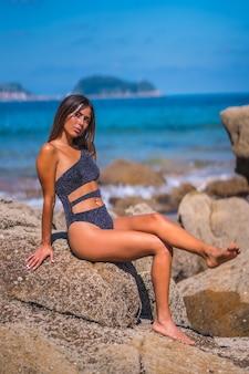 해변의 바위 옆에서 포즈를 취하는 동안 섹시한 수영복을 입은 여성의 세로 샷