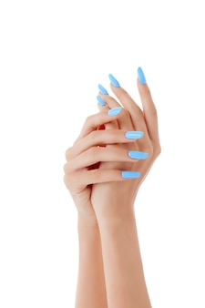 白い表面に青いマニキュアをした女性の手の垂直ショット