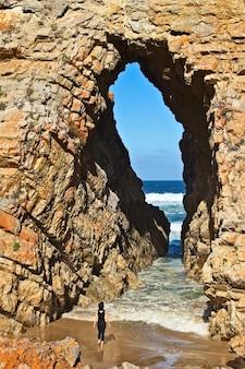 海につながる洞窟の前に立っている女性の垂直ショット