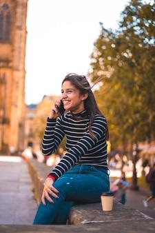 Вертикальный снимок женщины, говорящей по мобильному телефону
