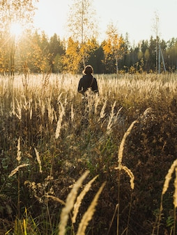 晴れた日に野生植物が付いている谷を歩く女性の垂直ショット
