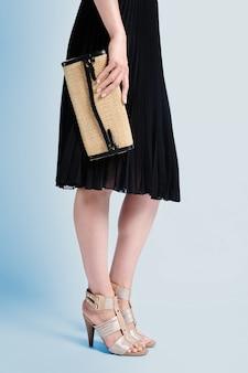Вертикальный снимок девушки в красивом черном платье и на высоких каблуках, держащей сумочку