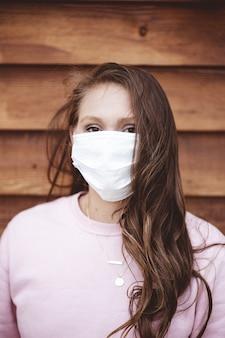 나무 벽 앞에 위생 얼굴 마스크를 쓰고 여성의 세로 샷