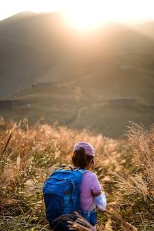 日没時に山でハイキングする大きなバックパックを持つ女性の垂直ショット