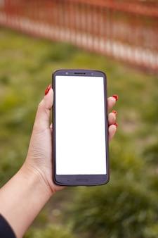 Вертикальный снимок женщины с красным лаком для ногтей, держащей телефон с пустым экраном