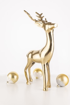 Вертикальный снимок статуи золотого оленя с шарами рождественского орнамента, изолированными на белом фоне