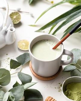 Вертикальный выброс зеленого чая маття на белом столе