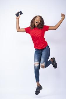 興奮してジャンプする幸せなアフリカの女性の垂直ショット