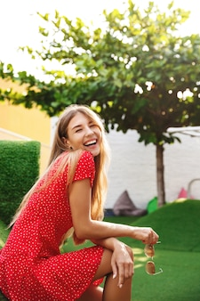 Вертикальный снимок счастливой красивой женщины, сидящей на траве в парке, смеющейся и улыбающейся в камеру